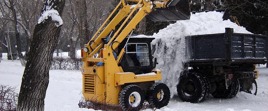 мини погрузчик грузит снег в самосвал